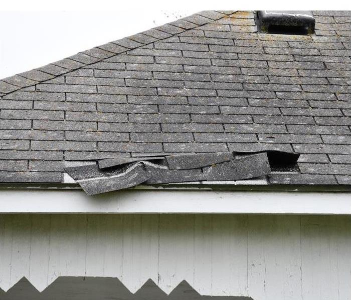 white house with black roof shingles damaged